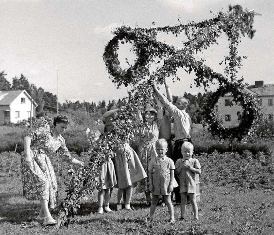 Midsommarfirande med familj som reser medsommarstången 1950-tal